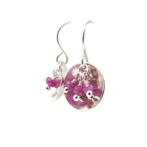 Dangle Earrings with Pink Sapphire gemstones hanging in a silver dish