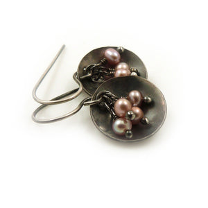 Dangle earrings with pink freshwater pearls hanging in an oxidised sterling silver dish