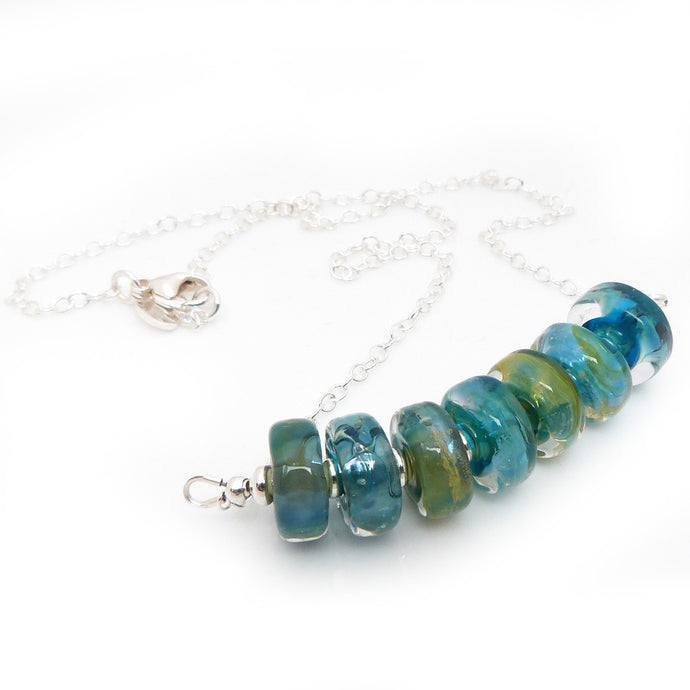 Sterling Silver Necklace with seven teal green lampwork glass beads