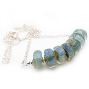 Silver necklace with seven aqua blue iridescent lampwork glass beads