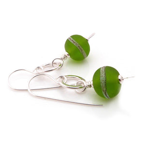 Dangle earrings with chunky donut shaped grass green lampwork glass beads hanging from sterling silver rings with silver hook earwires