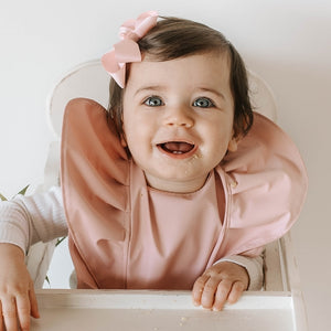 Little girl wearing waterproof pink bib and pink bow