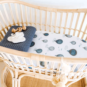 Rattan bassinet with cloud and hot air balloon sheet and folded blue blanket
