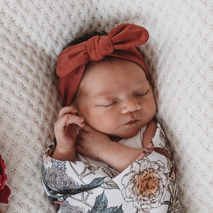 Newborn wearing a deep rust headband and floral swaddle