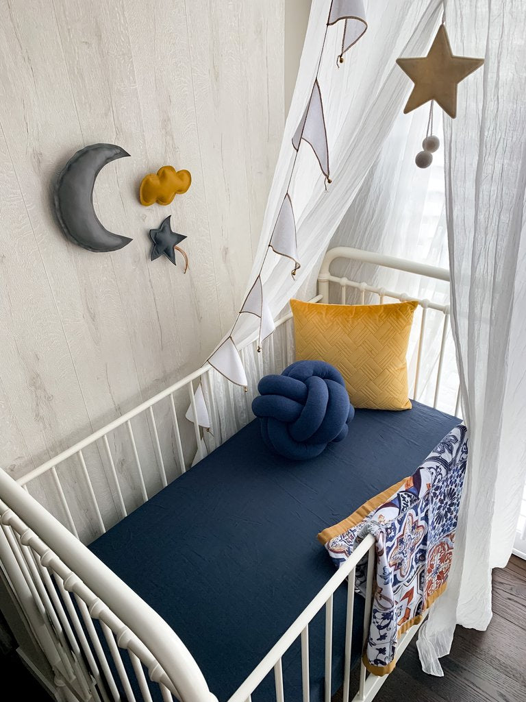 Faded Jeans Fitted cot sheet in a white cot