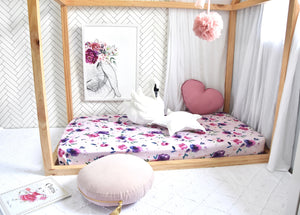 Pink and purple floral cot on wooden framed cot, with a white swan toy and nude round pillow and pink love heart pillow
