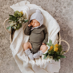 Baby in basket wearing a green outfit and grey bonnet and bootie set