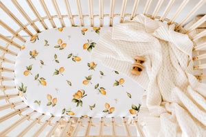 Lemon print bassinet sheet and cream knit blanket in rattan bassinet