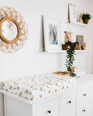 Lemon print change pad cover on white chest of drawers and mirror and pictures on wall