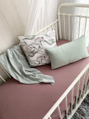 Mauve fitted cot sheet with pillows in a white cot