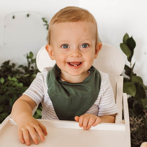 Little boy with wearing an olive dribble bib