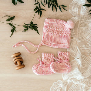 Pink merino wool bonnet and bootie set laying on a table and wooden rattle