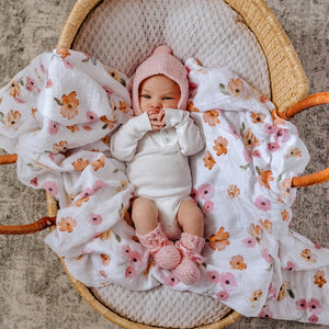 Baby girl laying on a floral swaddle wearing a white outfit and pink bonnet and bootie set