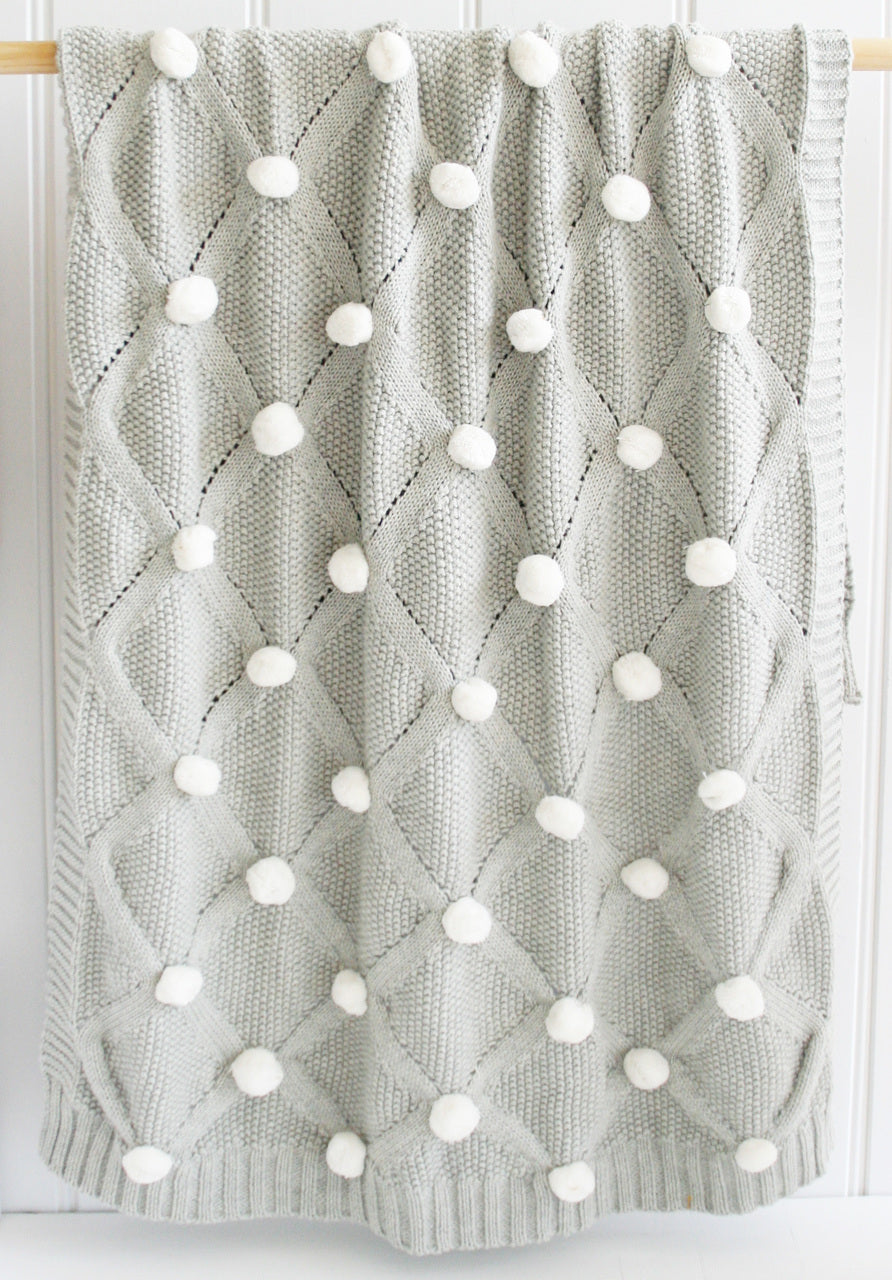 Grey knit baby blanket with ivory PomPoms