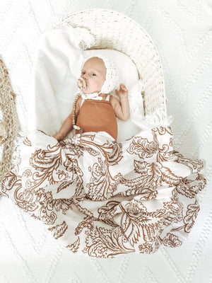 Baby in basket wrapped in  the Imperial Jacobean muslin swaddle