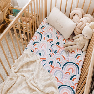 Rainbow fitted cot sheet in timber cot