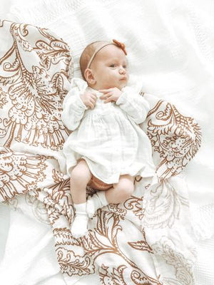 Baby girl laying on the Imperial Jacobean swaddle
