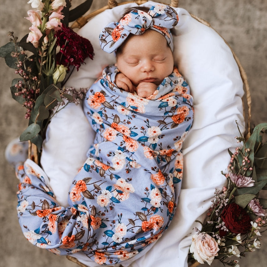 Baby girl wrapped in a floral Vintage Blossom jersey wrap and topknot headband