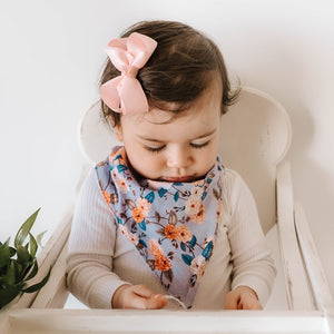 Little girl wearing a vintage blossom floral print and wearing a pink bow
