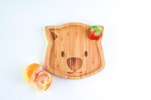 bamboo plate in the shape of a wombat face with a strawberry in the corner and mandarines next to the plate