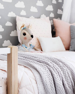 Grey knit blanket draped over white bed spread with teddy and pillows on it and grey and white cloud wall paper