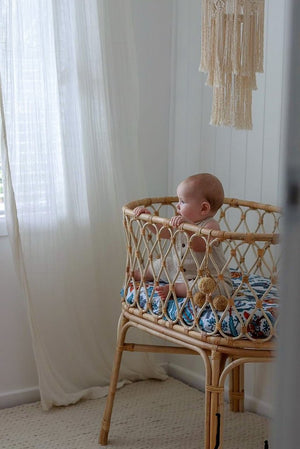 Wattle and Gum fitted bassinet sheet with rattan bassinet with a baby in it
