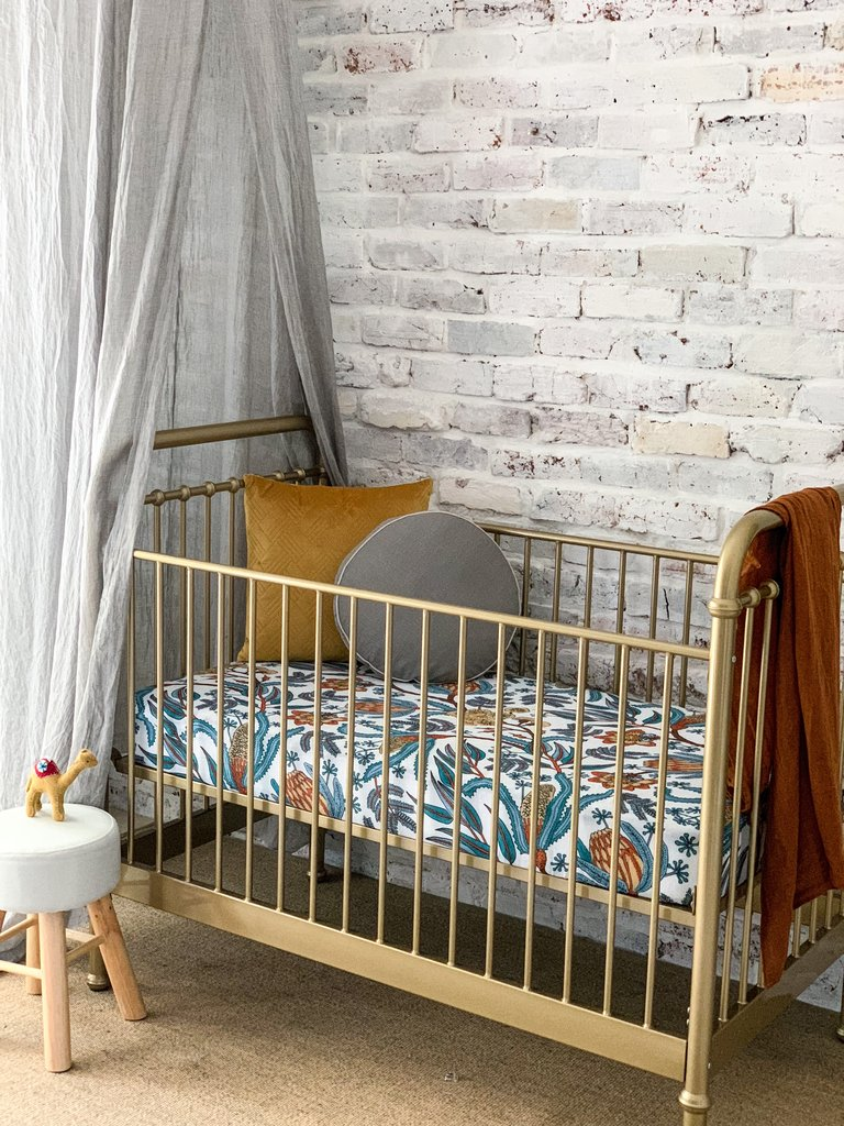 Wattle and gum cot sheet in gold cot with grey and mustard pillow