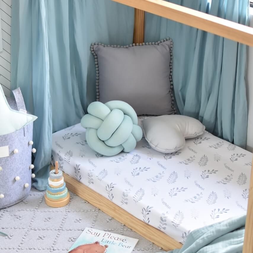 Toddler bed with white cot sheets which has ferns all over it, and has mint green canopy draped over toddler bed, grey basket sitting next to the bed and a stacker toy