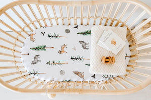 White bassinet sheet with pine trees, wolves and birds print on it, cream knit blanket and wooden rattle in bassinet