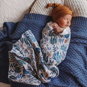 Newborn wrapped in a blue and white (arizona print) swaddle and mustard beanie, laying on a blue knit blanket