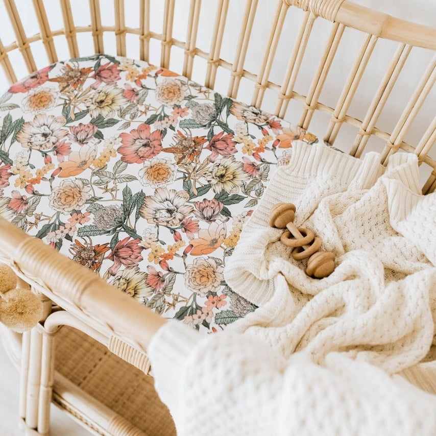 Australian floral pinks, orange, blue, green bassinet sheet and cream knit blanket in rattan bassinet