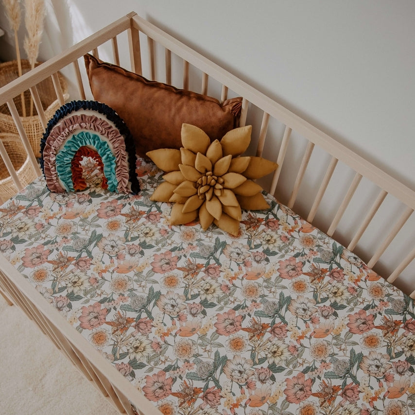 Australiana fitted cot sheet, floral pattern with pinks, orange and green colours, three pillows sitting in a wooden cot