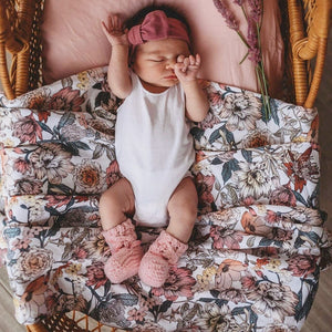 Newborn girl laying on Australiana floral print wrap and wearing a mauve pink bow
