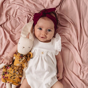 Baby girl with burgundy topknot headband laying on pink swaddle with a bunny rabbit