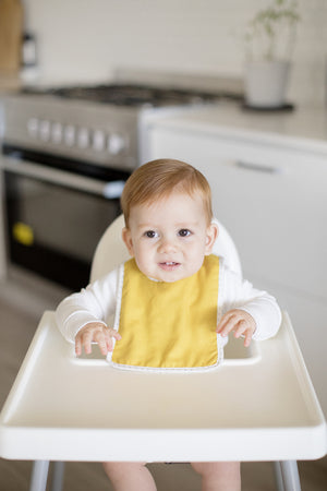 Baby wearing butterscotch linen bib