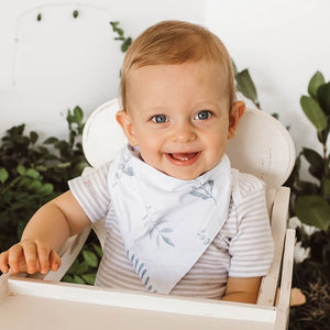Little boy wearing a white dribble bib with green ferns on it
