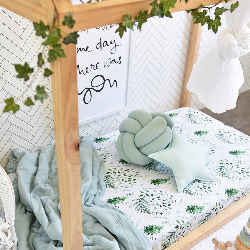 timber cot with a green and white leafy cot sheet, mint green blanket and ball and star pillow laying on it