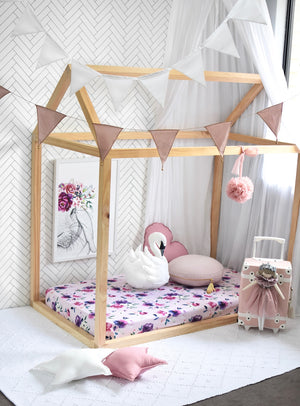a wooden house framed cot with a pink and purple floral cot sheet, with a swan toy, pink heart pillow and nude round pillow, bunny artwork on the wall and bunting hanging from the ceiling