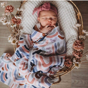 baby in basket wrapped in rainbow swaddle