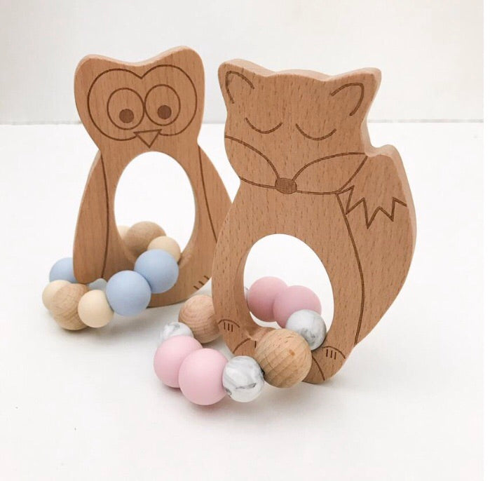 Fox silicone and beech wood teether, pink and white silicone beads and owl beechwood teether in background