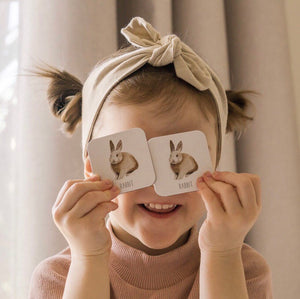 Little girl holding two woodland memory cards with foxes on them