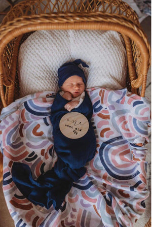 Baby in a basket wrapped in navy swaddle and laying on a rainbow swaddle