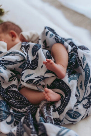 baby laying on bed with a blue beanie and blue and white swaddle