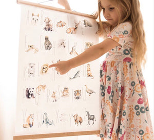Animal alphabet print held by a little girl