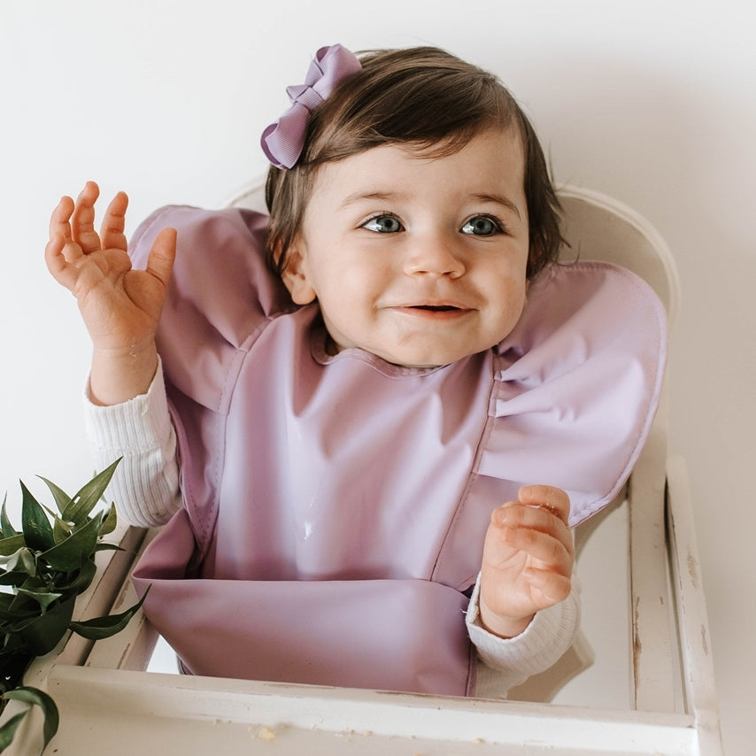 Girl toddler with purple bib on and purple bow in hair