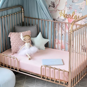 Gold cot with pink cot sheets, three pillows and a doll sitting on cot, floral wall paper in background and green canopy