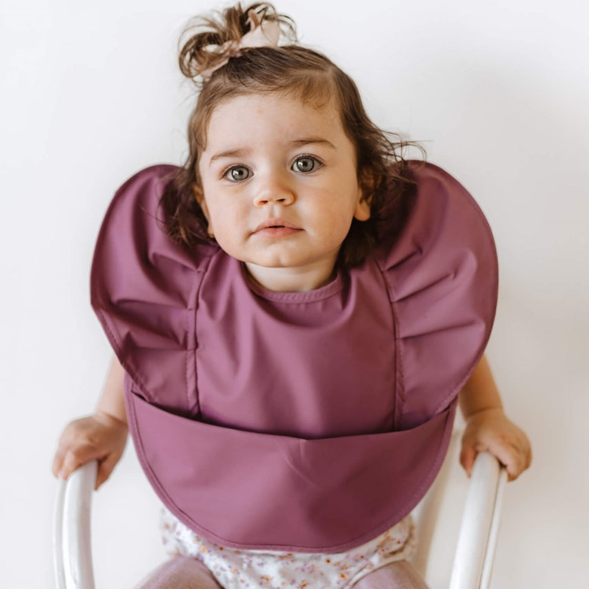 Mauve Snuggle Hunny Bib on a little girl