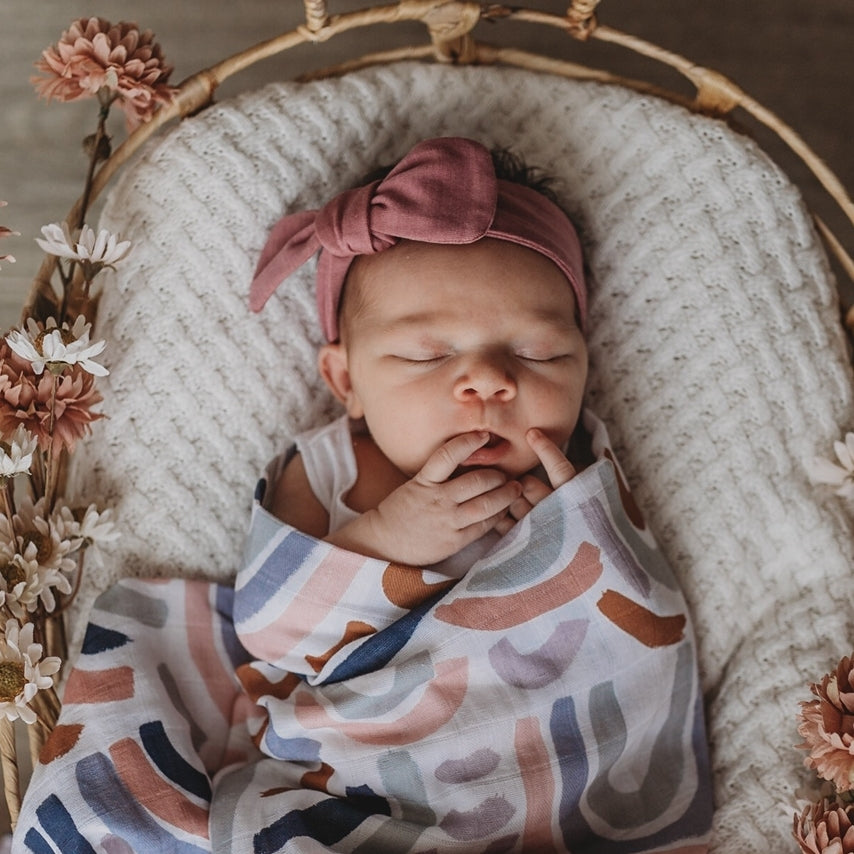 Baby girl in basket wearing a mauve topknot headband and rainbow swaddle