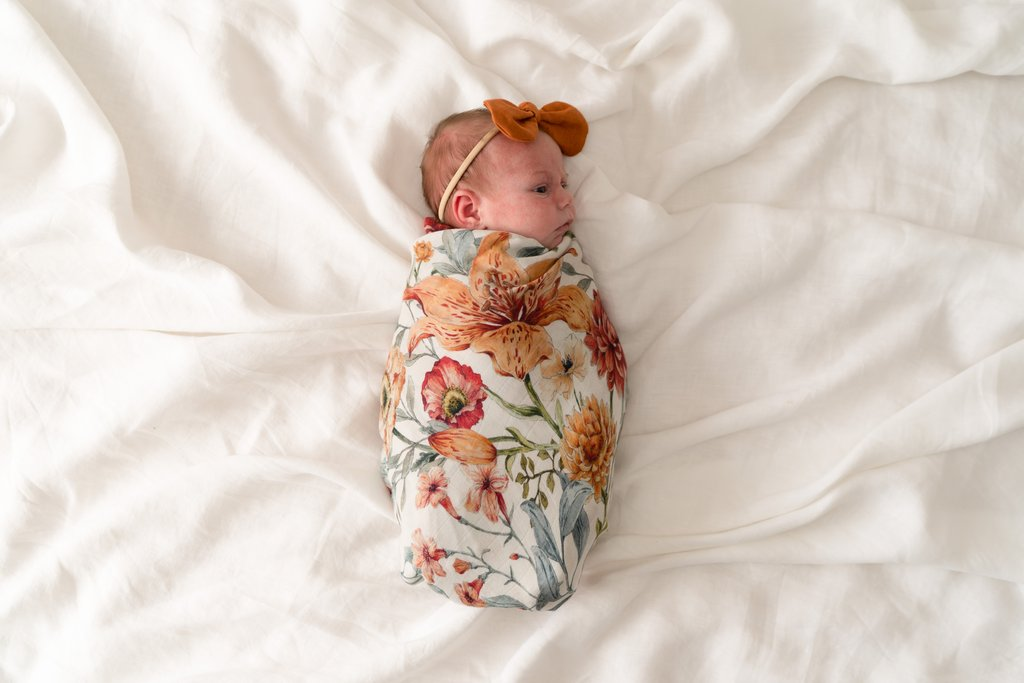 PopYaTo floral muslin swaddle wrapped around a newborn baby girl