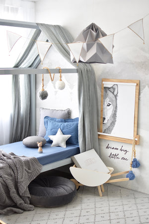 Toddler bed with blue reign cot sheet, pillows and blanket on it, wolf art work on the wall